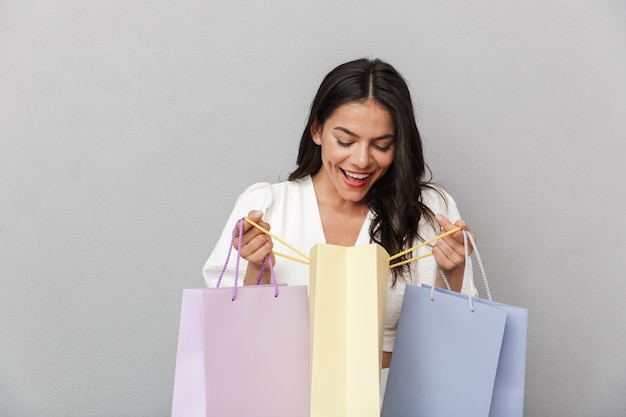 Retrato de uma linda jovem morena com roupa de verão, em pé, isolado na parede cinza, carregando sacolas de compras