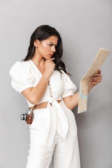 Retrato de uma linda jovem morena com roupa de verão, em pé, isolado na parede cinza, olhando para o mapa de viagens