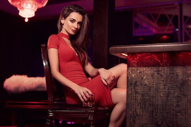 Retrato de uma linda jovem morena de vestido vermelho sentada no bar