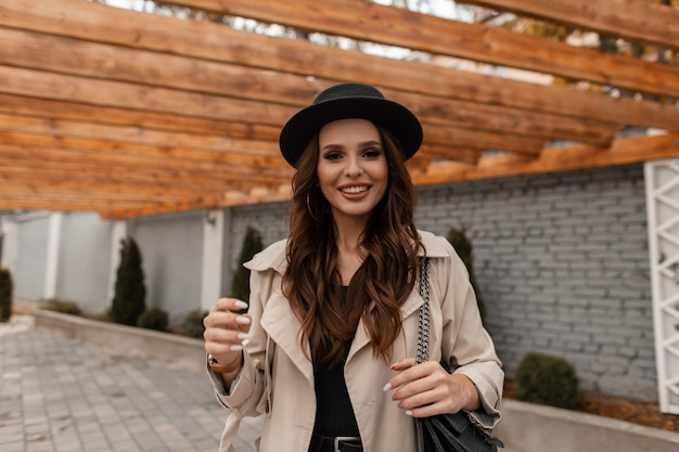 Retrato de uma linda jovem morena encaracolada com sorriso fofo em um chapéu da moda com um elegante casaco vintage e uma bolsa de couro anda na rua. estilo feminino elegante, moda e beleza