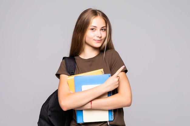 Retrato de uma linda jovem morena estudante segurando cadernos de exercícios isolados na parede branca