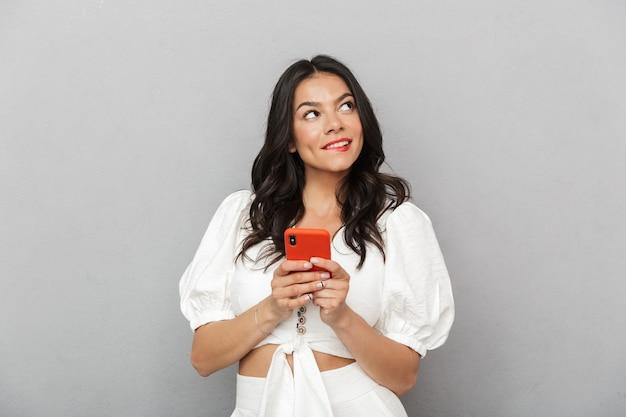 Retrato de uma linda jovem morena pensativa, vestindo uma roupa de verão, em pé, isolado na parede cinza, segurando um telefone celular