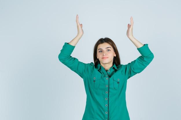 Retrato de uma linda jovem mostrando um gesto de impotência em uma camisa verde e olhando perplexo com a vista frontal