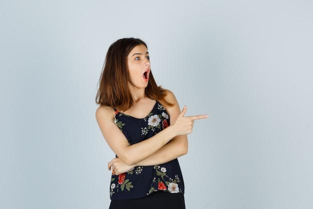 Retrato de uma linda jovem mulher apontando para a direita na blusa, saia e olhando a vista frontal chocada