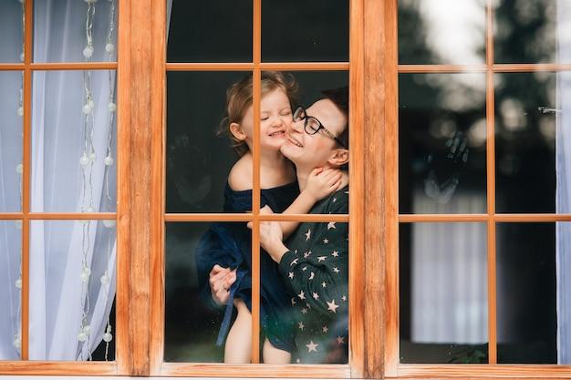 Retrato de uma linda jovem mulher com rosto bonito, cabelo escuro curto, olhos grandes, óculos com seu filho alegre