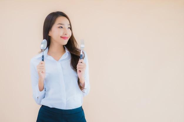 Retrato de uma linda jovem mulher de negócios asiática com colher e garfo prontos para comer