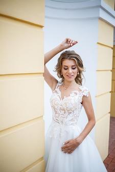 Retrato de uma linda jovem no dia do casamento da noiva, vestida com um vestido de noiva branco no fundo de uma grande casa com colunas