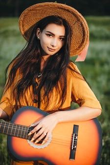 Retrato de uma linda jovem olhando para a câmera sorrindo. mulher caucasiana atraente segurando um violão cantando na natureza lá fora.