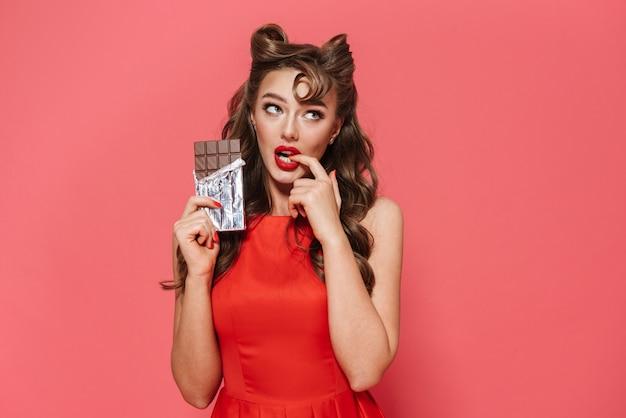 Retrato de uma linda jovem pin-up com vestido de pé isolado, comendo barra de chocolate