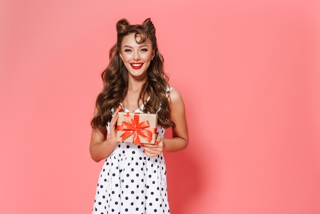 Retrato de uma linda jovem pin-up usando um vestido de pé isolado, mostrando uma caixa de presente
