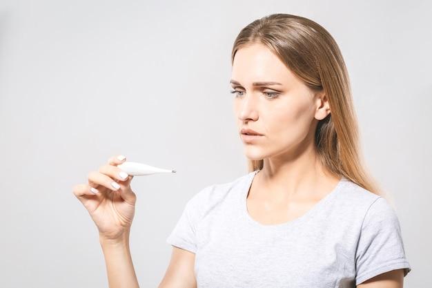 Retrato de uma linda jovem preocupada, verificando sua temperatura. fundo branco, gripe.