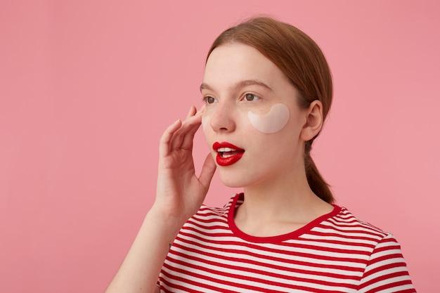 Retrato de uma linda jovem ruiva com lábios vermelhos e com manchas sob os olhos, usa uma camiseta listrada vermelha, desvia o olhar e pensa em um vestido novo, fica de pé.