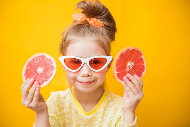 Retrato de uma linda jovem segurando duas partes de toranja cortada perto de seu rosto, fundo amarelo. conceito de frescor saudável