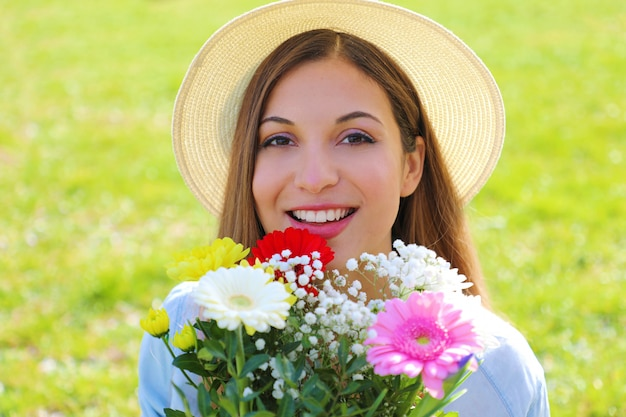 Retrato de uma linda jovem segurando um buquê de flores e isolada no fundo da grama verde