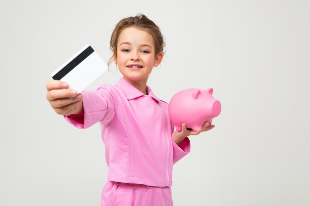 Retrato de uma linda jovem sorridente em um terno rosa, mostrando um cofrinho e cartão de crédito com uma maquete em um branco