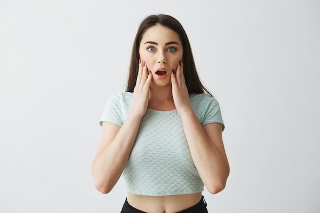 Retrato de uma linda jovem surpreso com a boca aberta, com as mãos nas bochechas.