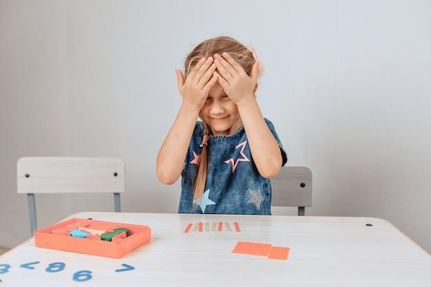 Retrato de uma linda linda princesa menina sentada em uma mesa rodeada por um grande número de quebra-cabeças e fechando os olhos de excitação. conceito de progresso. foto com ruído