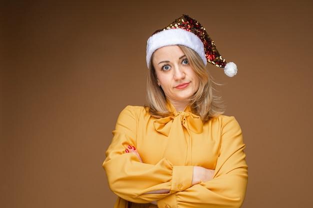 Retrato de uma linda loira caucasiana com um chapéu de papai noel cintilante e uma blusa amarela com os braços cruzados em indignação