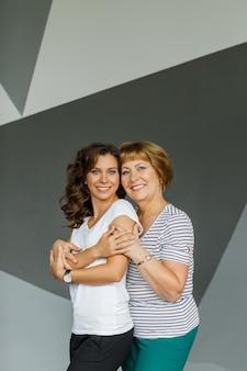 Retrato de uma linda mãe madura e sua filha se abraçando, sorrindo, posando para a câmera no estúdio
