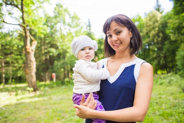 Retrato de uma linda mãe sorridente feliz com o bebê ao ar livre.