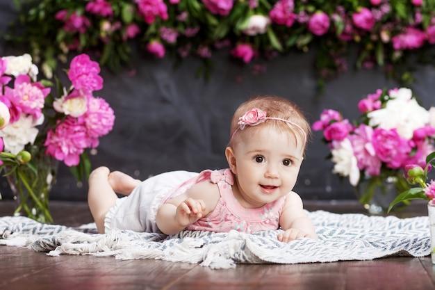 Retrato de uma linda menina com flores cor de rosa. menina doce e sorridente deitada de bruços