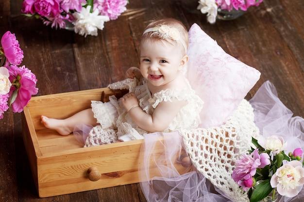 Retrato de uma linda menina com flores cor de rosa. menina doce e sorridente sentada em uma caixa de madeira no chão