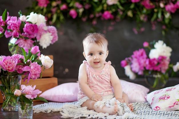 Retrato de uma linda menina com flores cor de rosa. menina doce e sorridente sentada no chão