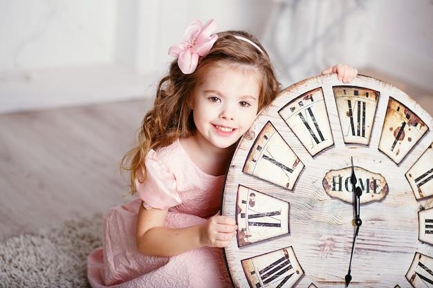 Retrato de uma linda menina com longos cabelos crespos em um vestido rosa com um grande relógio esperando o ano novo