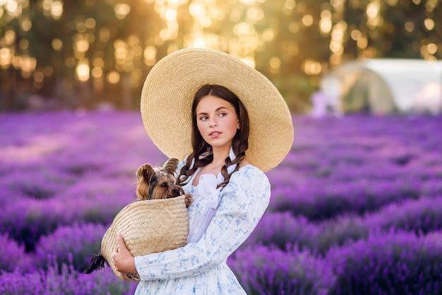 Retrato de uma linda menina com um cachorro em uma cesta em um fundo de lavanda. ela está usando um vestido branco e um chapéu grande.
