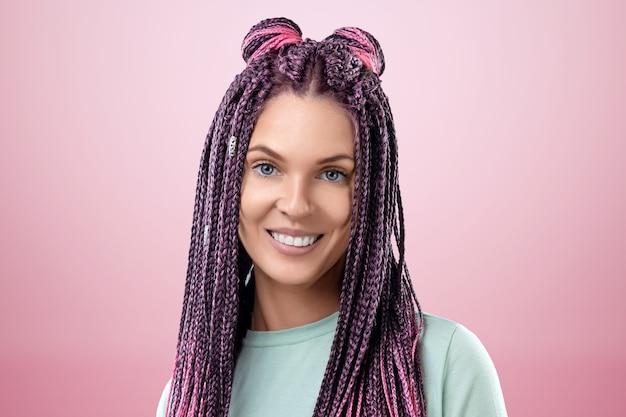 Retrato de uma linda menina com um penteado de tranças cor de rosa com roupas turquesas, posando em um fundo rosa no estúdio. o conceito é estilo moderno, individualidade, abrangência, criatividade.
