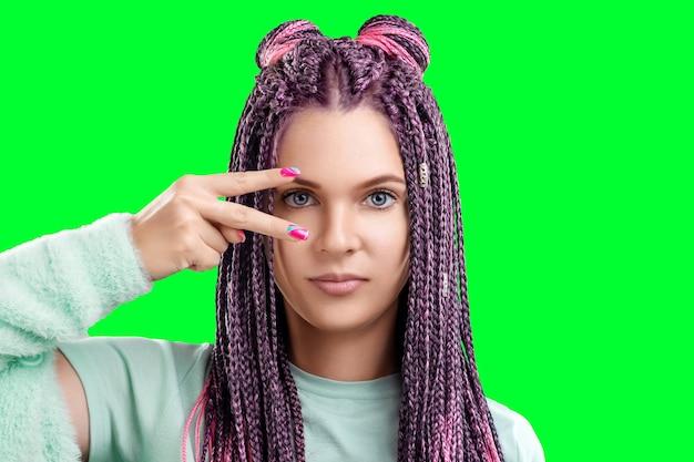 Retrato de uma linda menina com um penteado de tranças rosa em roupas turquesas isolar sobre um fundo verde. o conceito é estilo moderno, individualidade, abrangência, criatividade.