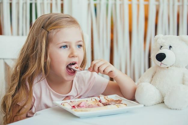 Retrato de uma linda menina com um ursinho de pelúcia em um café, comendo um delicioso sorvete.