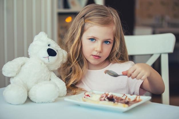 Retrato de uma linda menina com um ursinho de pelúcia em um café tomando sorvete.