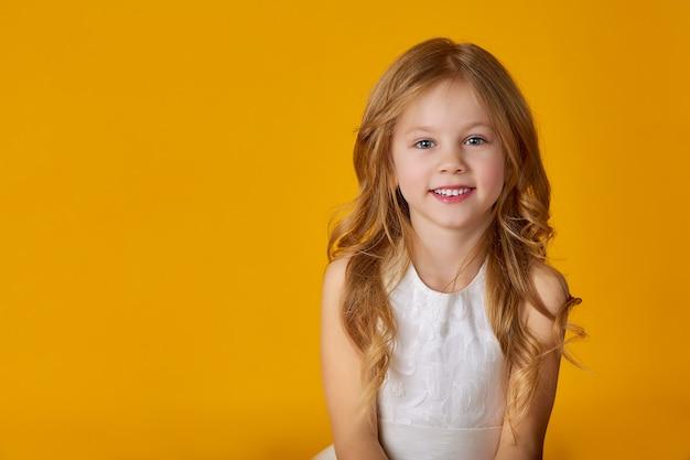Retrato de uma linda menina de 6 anos em um vestido branco posando em um amarelo brilhante