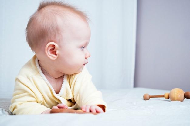 Retrato de uma linda menina de sete meses com olhos azuis. uma criança brinca com brinquedos de madeira em uma sala iluminada. brinquedos ecológicos para crianças feitos de materiais naturais.