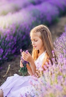 Retrato de uma linda menina em um campo de lavanda. foto de verão nas cores roxas.