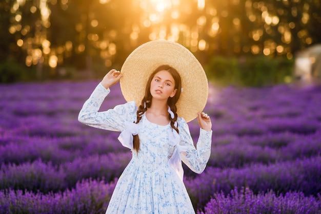 Retrato de uma linda menina em um fundo de lavanda. ela está usando um vestido branco e um chapéu grande. foto de verão ao sol