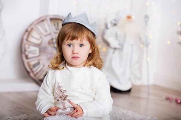 Retrato de uma linda menina em um vestido branco e uma coroa no interior com enfeites de natal. princesinha com uma árvore de natal de brinquedo de madeira