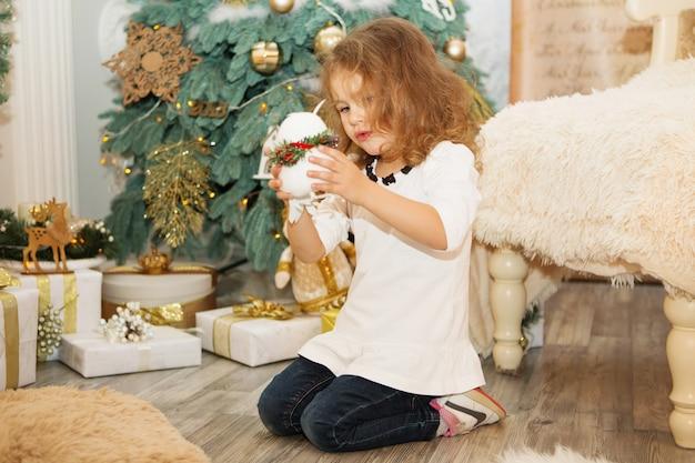 Retrato de uma linda menina entre as decorações de natal