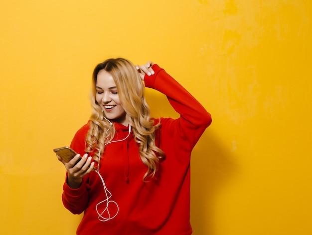 Retrato de uma linda menina feliz loira ouvindo música em fones de ouvido e dançando na parede amarela