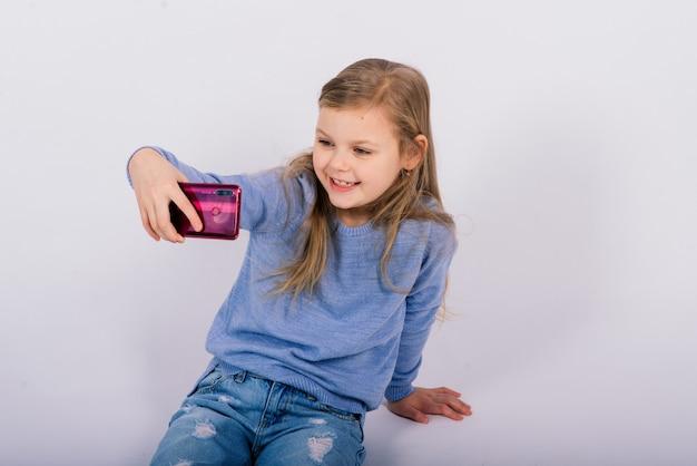 Retrato de uma linda menina feliz sorrindo em um estúdio. fundo branco isolado