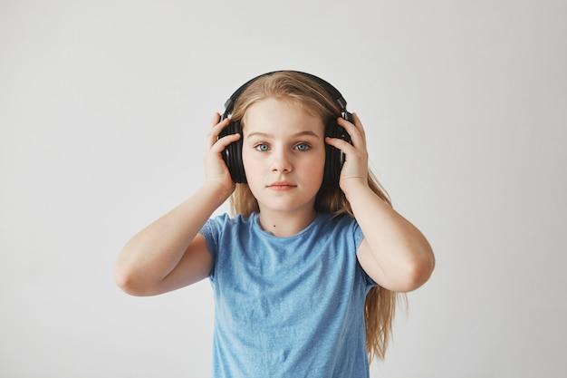 Retrato de uma linda menina loira com cabelos longos e olhos azuis, usando fones de ouvido grandes, segurando-o com as mãos, ouvindo música com expressão relaxada.