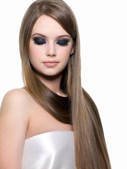 Retrato de uma linda menina loira com uma maquiagem brilhante nos olhos e um lindo cabelo longo e reto