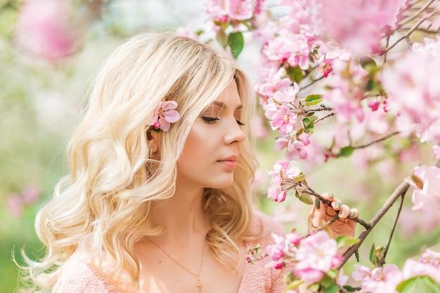 Retrato de uma linda menina loira em um jardim de primavera. flores de maçã rosa