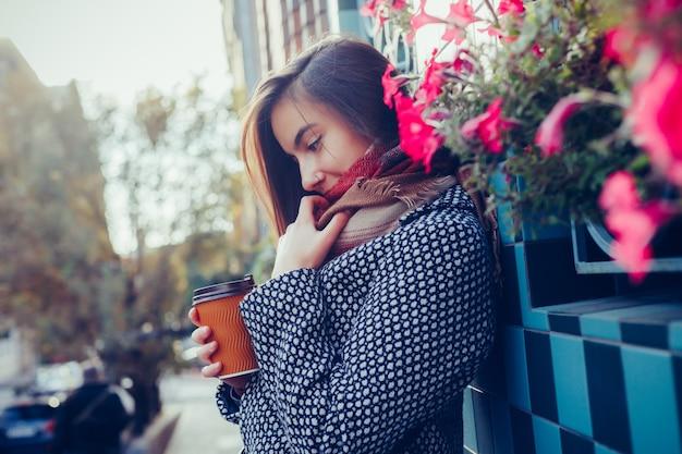 Retrato de uma linda menina morena com bebida para viagem na rua. lenço e casaco de outono na cidade. vista incrível da mulher de negócios com uma xícara de café, descendo a rua da cidade.