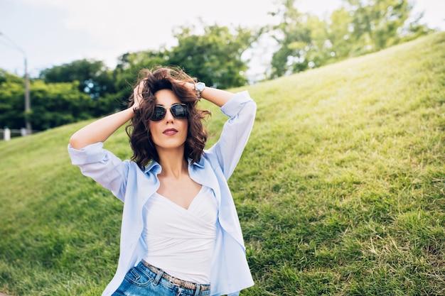 Retrato de uma linda menina morena com cabelo curto em óculos de sol, posando para a câmera no parque no fundo do prado. ela usa camiseta branca, camiseta azul.