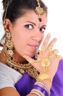 Retrato de uma linda menina morena com cabelos longos, em roupas tradicionais azuis indianas. joias enormes no rosto e perto. isolado em fundo branco