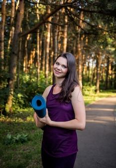 Retrato de uma linda menina morena com um tapete de ioga no caminho no parque