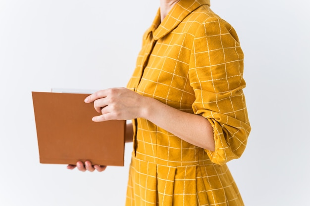 Retrato de uma linda menina morena com um vestido retrô amarelo lendo um livro