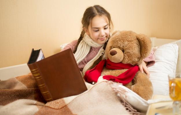 Retrato de uma linda menina morena contando uma história para um ursinho de pelúcia na cama